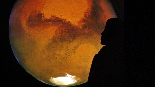 A Jordanian boy poses with an image of Mars projected on a wall in Amman
