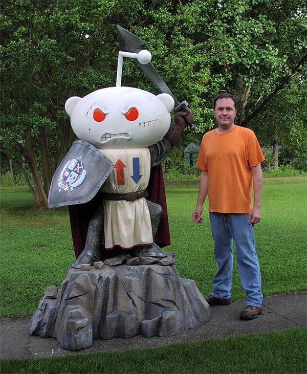 Statue designer Richard Riley posing with his creation