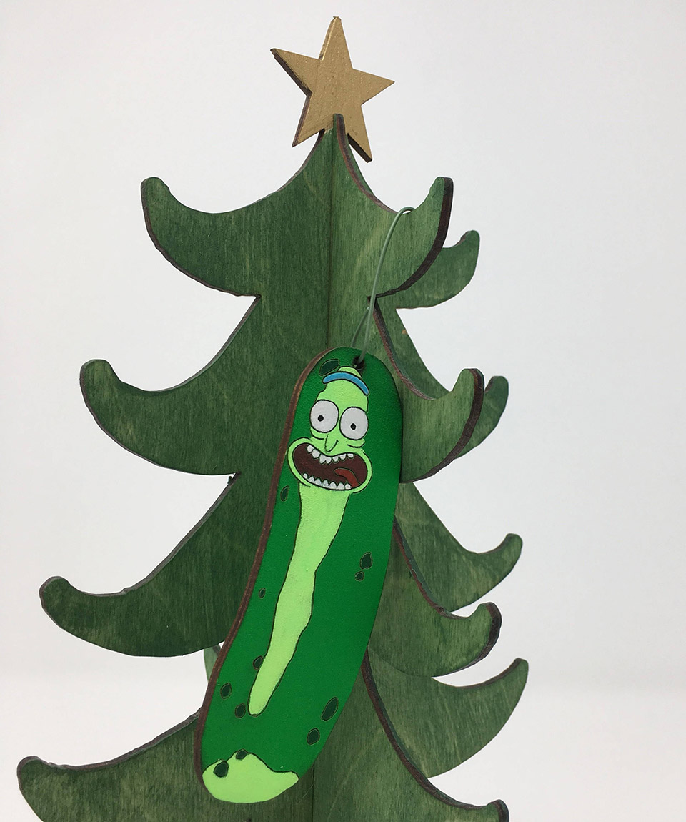telestic design is making these fun handpainted wood ornaments featuring the likeness of pickle rick which will look great hanging in your tree alongside